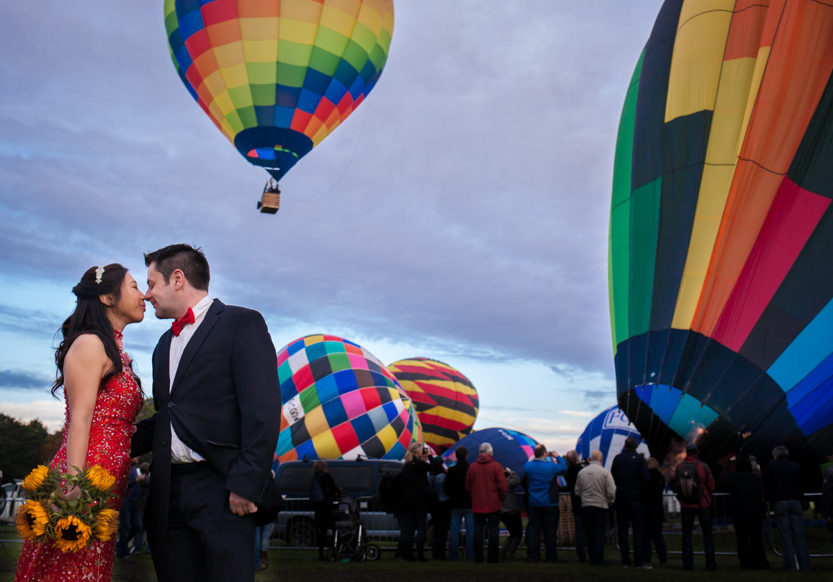 Bride in red dress and groom touching noses in front of hot air balloons