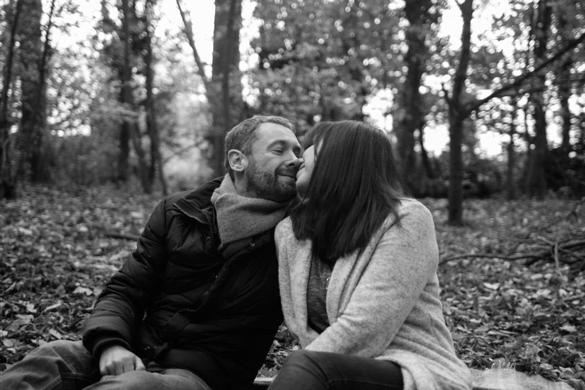 Couple kissing in autumnal woodland black and white