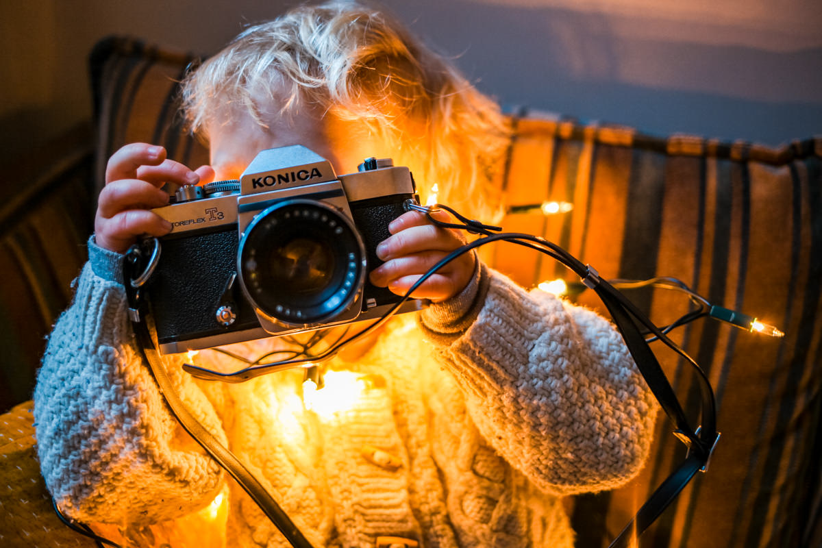 Little boy playing with analog camera with fairy lights around him
