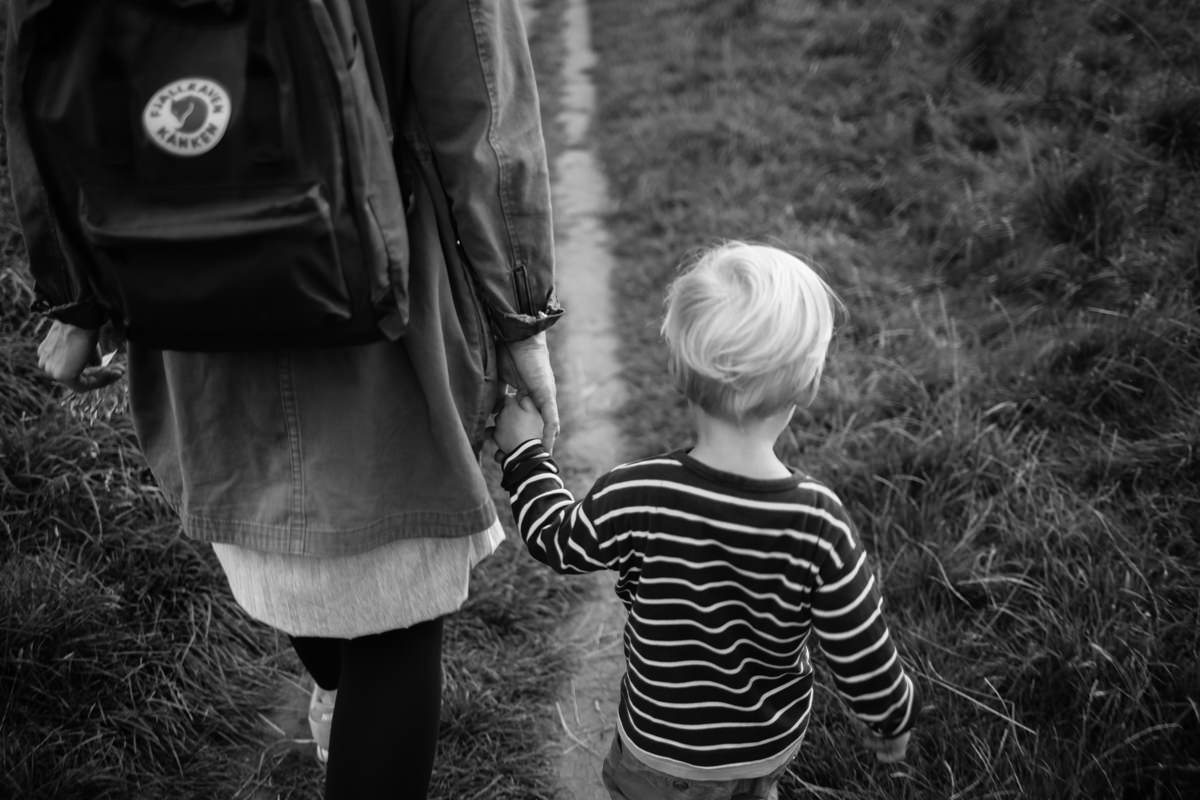 Little boy holding hands with mother walking along country path black and white