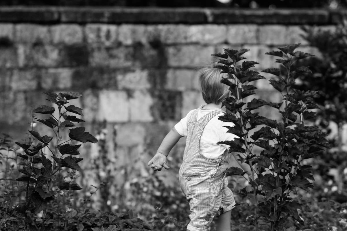 Little boy running through bushes in front of wall black and white