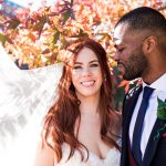 Wedding couple under autumnal tree with sun in background shining through veil smiling