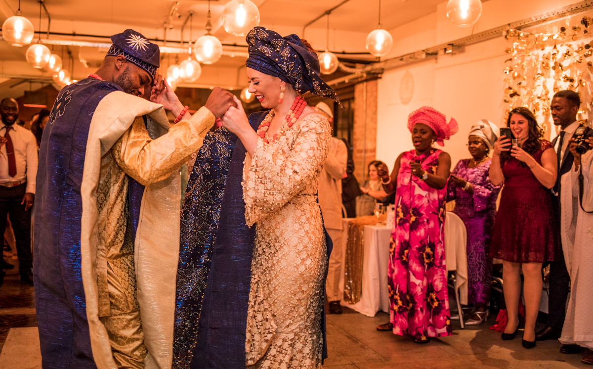 Wedding couple in Nigerian outfits dancing first dance in warmly lit room with big lights