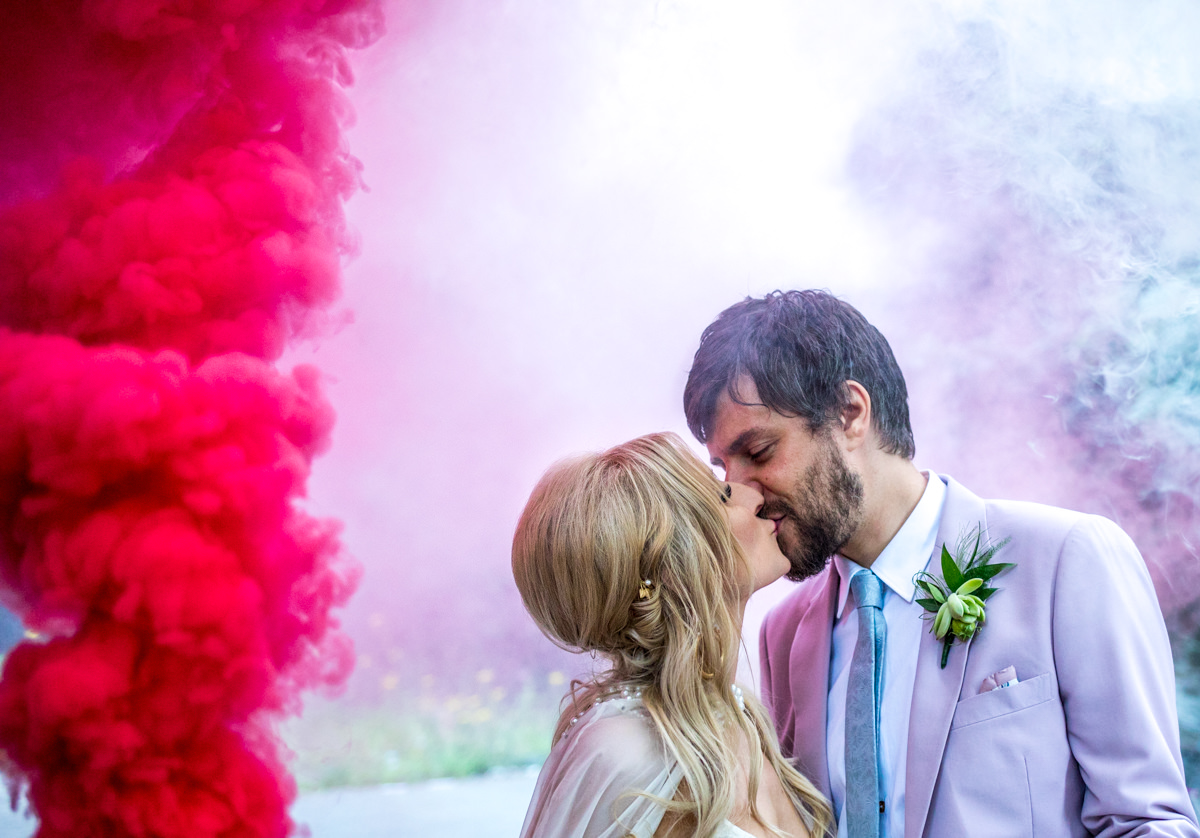 Bride and groom kissing in front of red and white smoke bombs