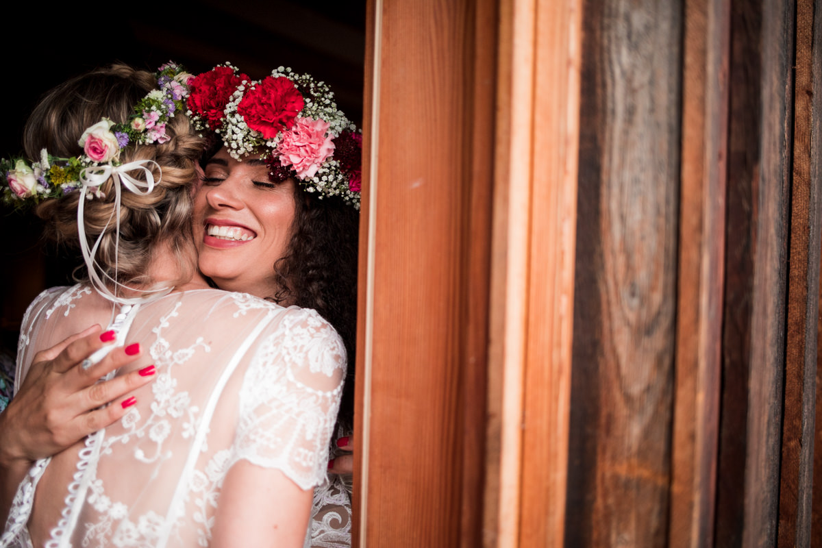 Two brides with flower crown hugging next to farm wooden wall