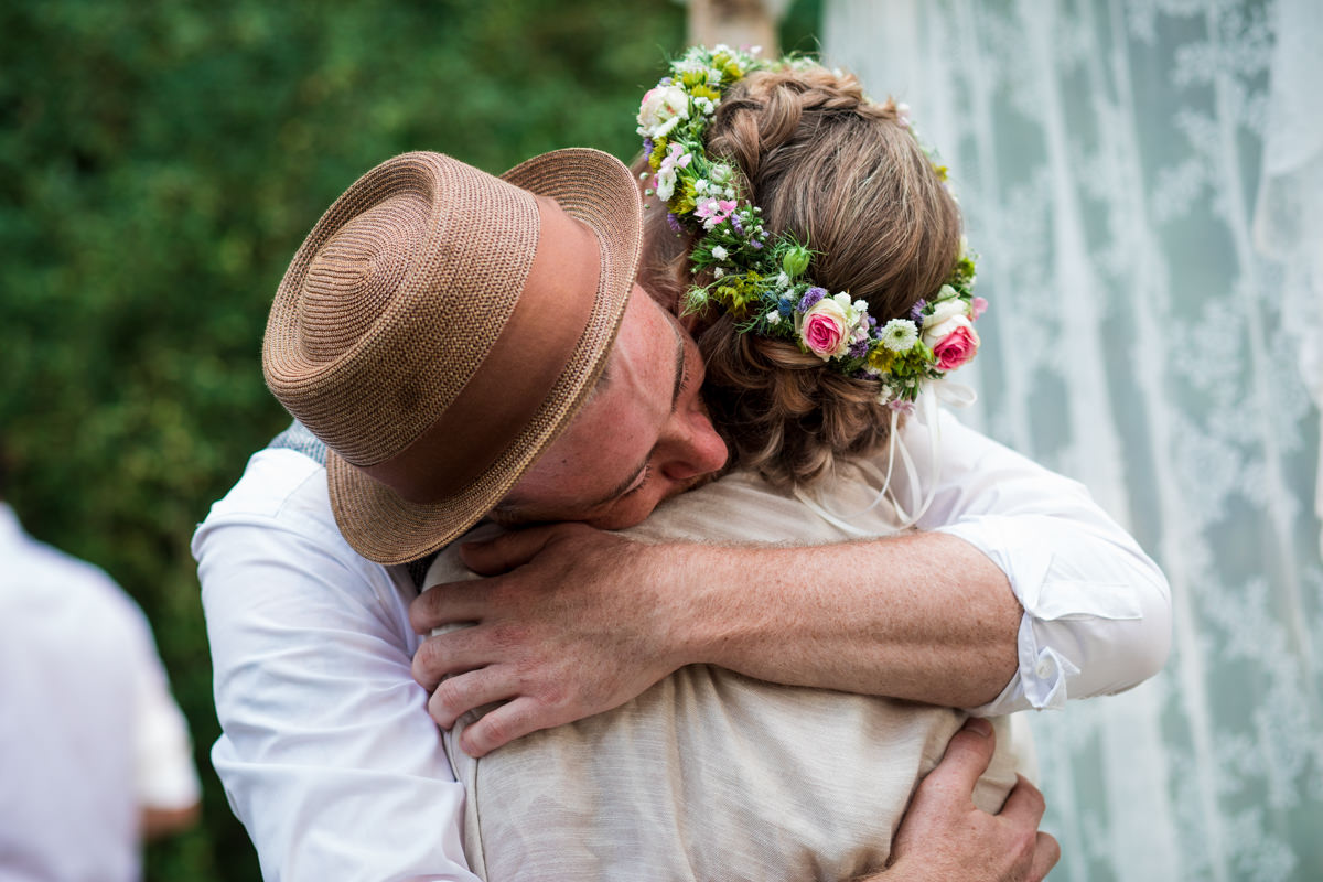 Groom with hat hugging bride with flower crown at countryside ceremony