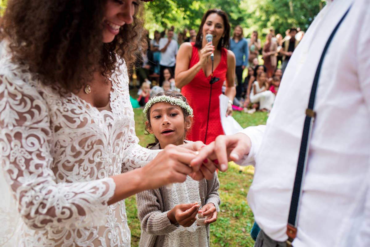 Bride putting ring on grooms finger with little bridesmaid with flower crown looking intrigued in the background