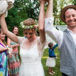 Happy bride and groom with hands in air smiling leaving ceremony