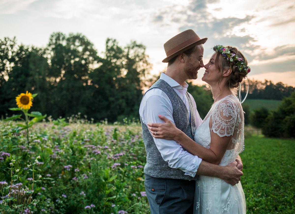Relaxed bride and groom looking at each other in sunset in front of field smiling
