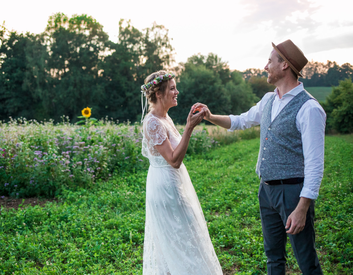 Relaxed bride and groom dancing in sunset in front of field smiling at each other