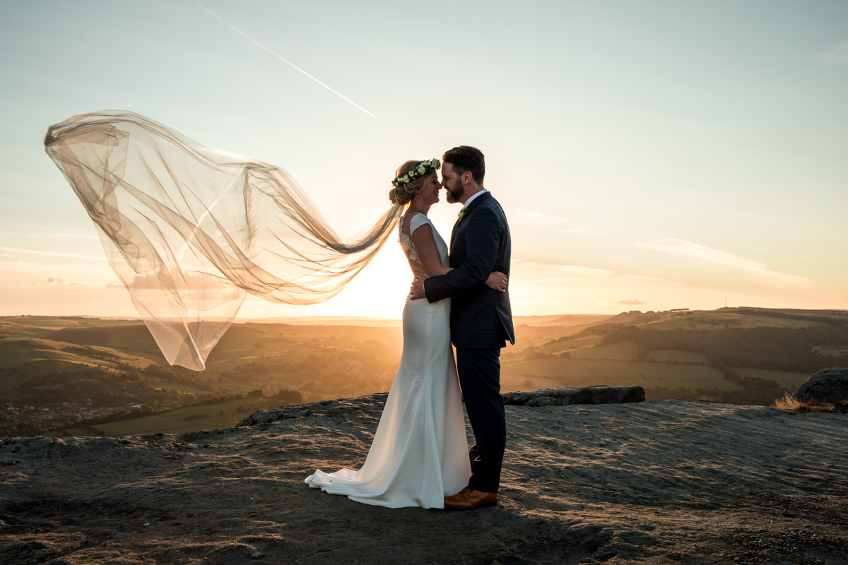 Wedding couple on Curbar edge in front of sunset with wind blowing in veil