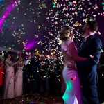 Yorkshire wedding couple first dance in marquee looking up at colourful confetti canons
