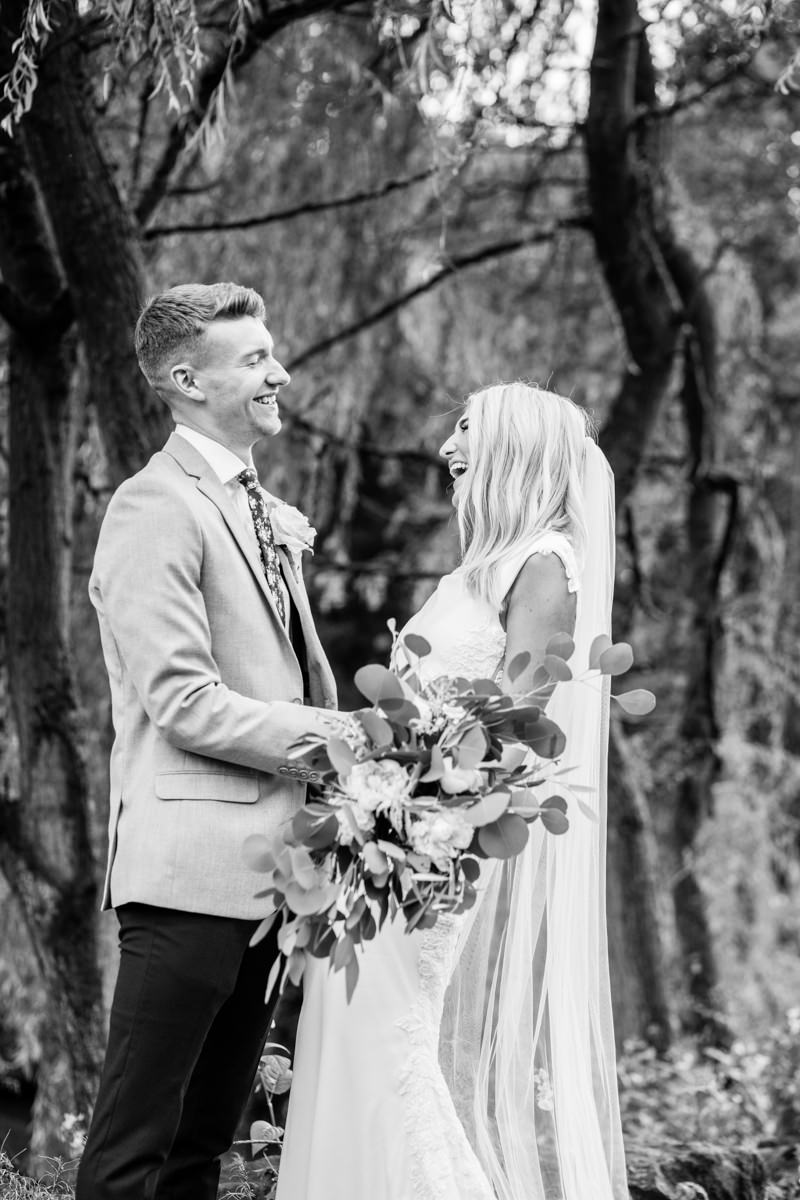 Relaxed wedding couple in front of trees smiling at each other bride holding big bouquet