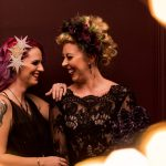 Two brides with wintery headdresses and black wedding dresses smiling at each other in front of red wall with fairy lights in foreground