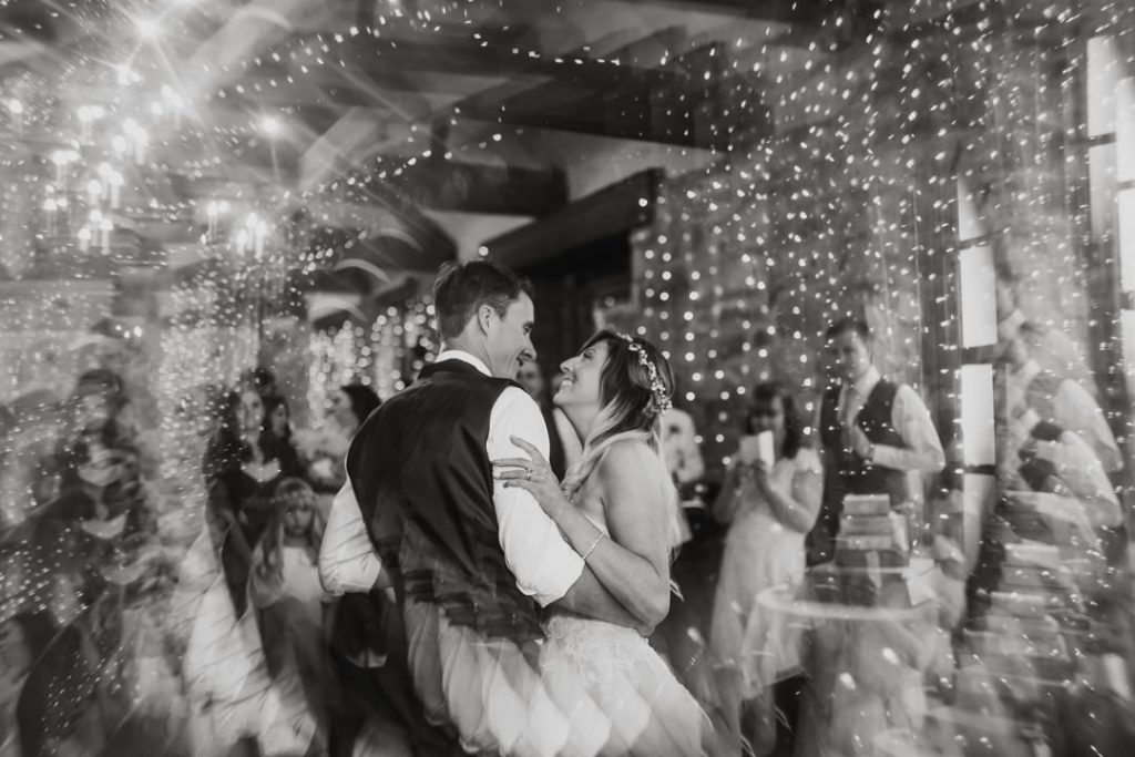Happy bride and groom dancing first dance smiling surrounded by lights