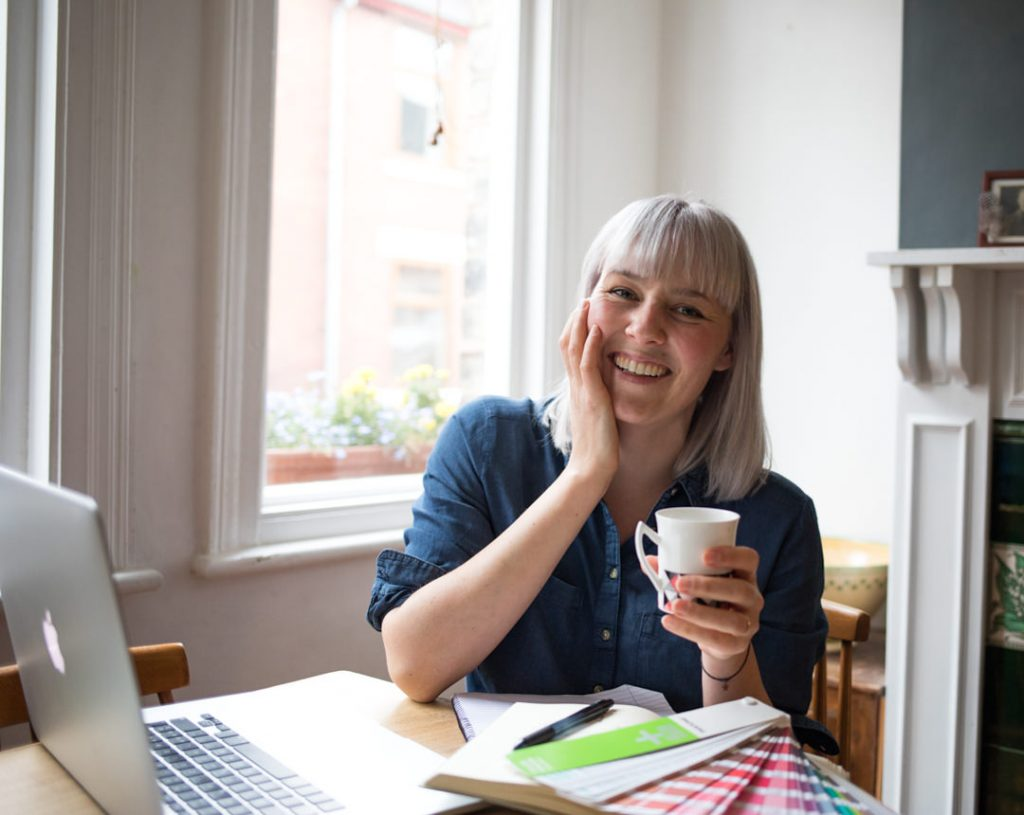 Blond woman graphic designer smiling whilst working at desk