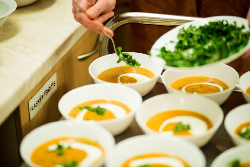 Product photography yellow soup being dressed with parsley and joghurt