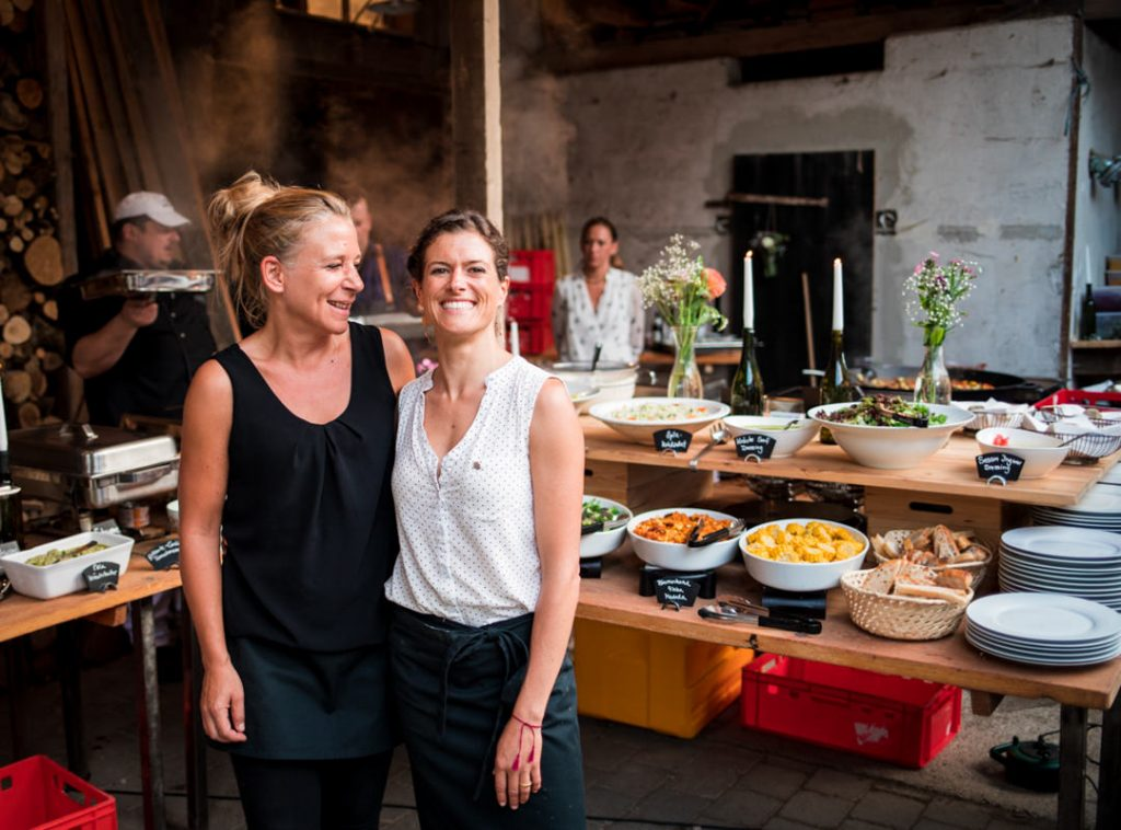 Two woman smiling in front of wedding catering