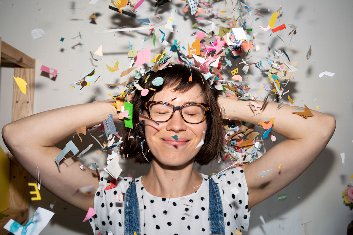 Elena Wagner with eyes closed with paper snippets falling down on her