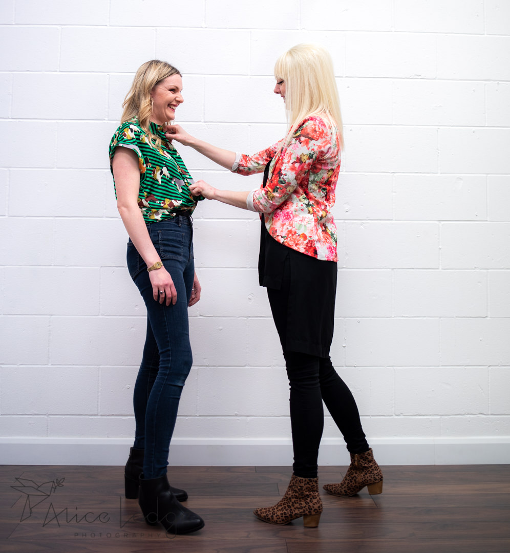 A blond woman helping another woman wit personal styling in front of white wall