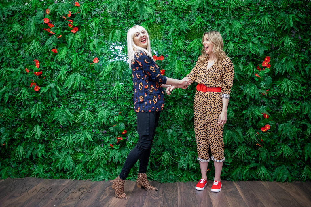 Two women in front of green flower wall laughing