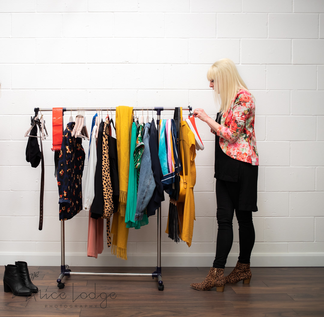 Blond woman in floral jacket standing next to clothes rack sorting through clothes