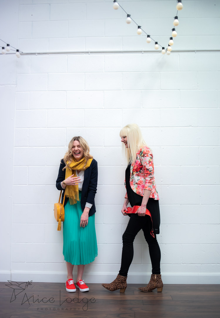 A blond woman helping another woman in green skirt wit personal styling in front of white wall