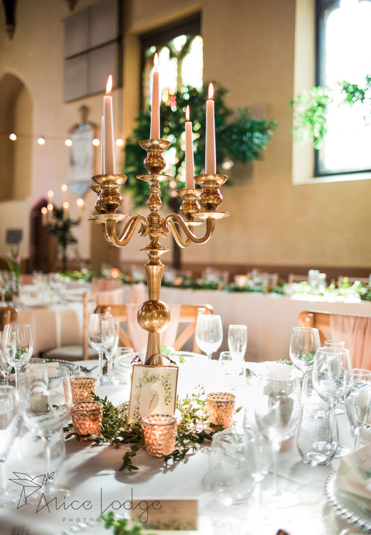 National centre for early music wedding table centre piece gold chandelier rose gold candles wine glasses white napkins