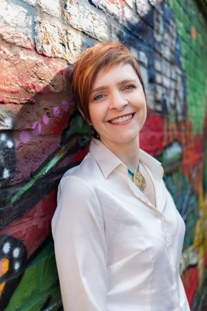 Andrea Morrison coaching leaning against colourful wall wearing white blouse smiling