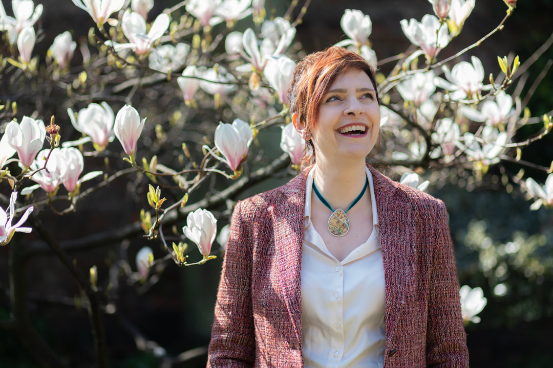Andrea Morrison coaching standing in front of magnolia tree looking up and smiling