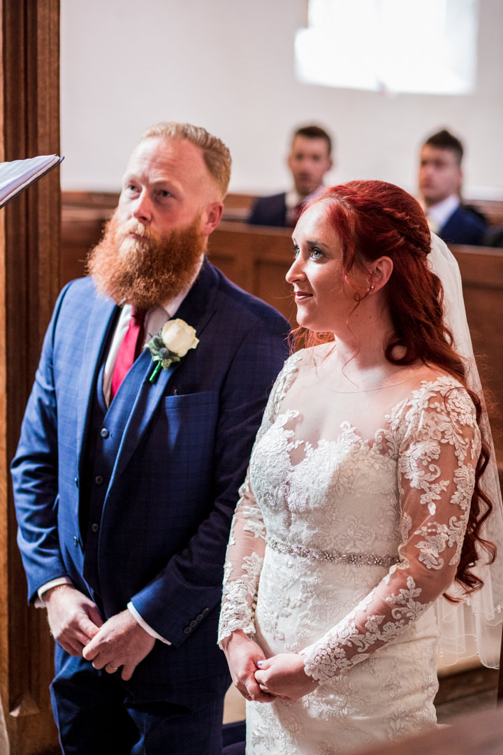 Bride and groom kneeling in church looking up to vicar