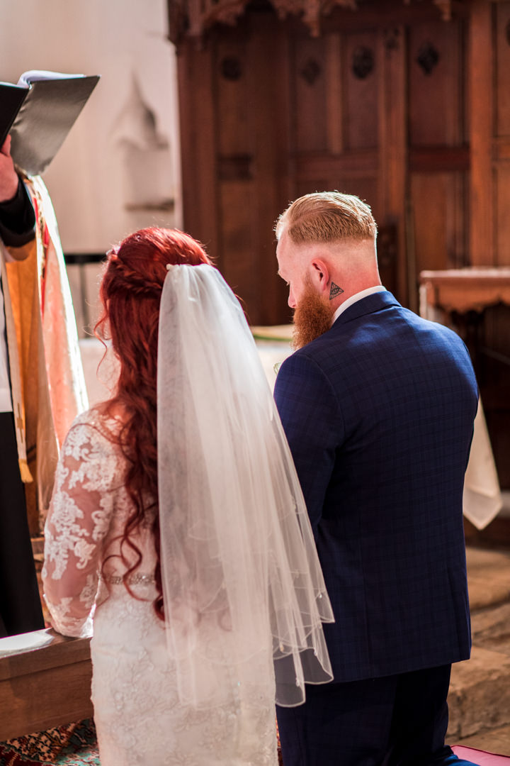 Bride and groom kneeling in church looking down praying