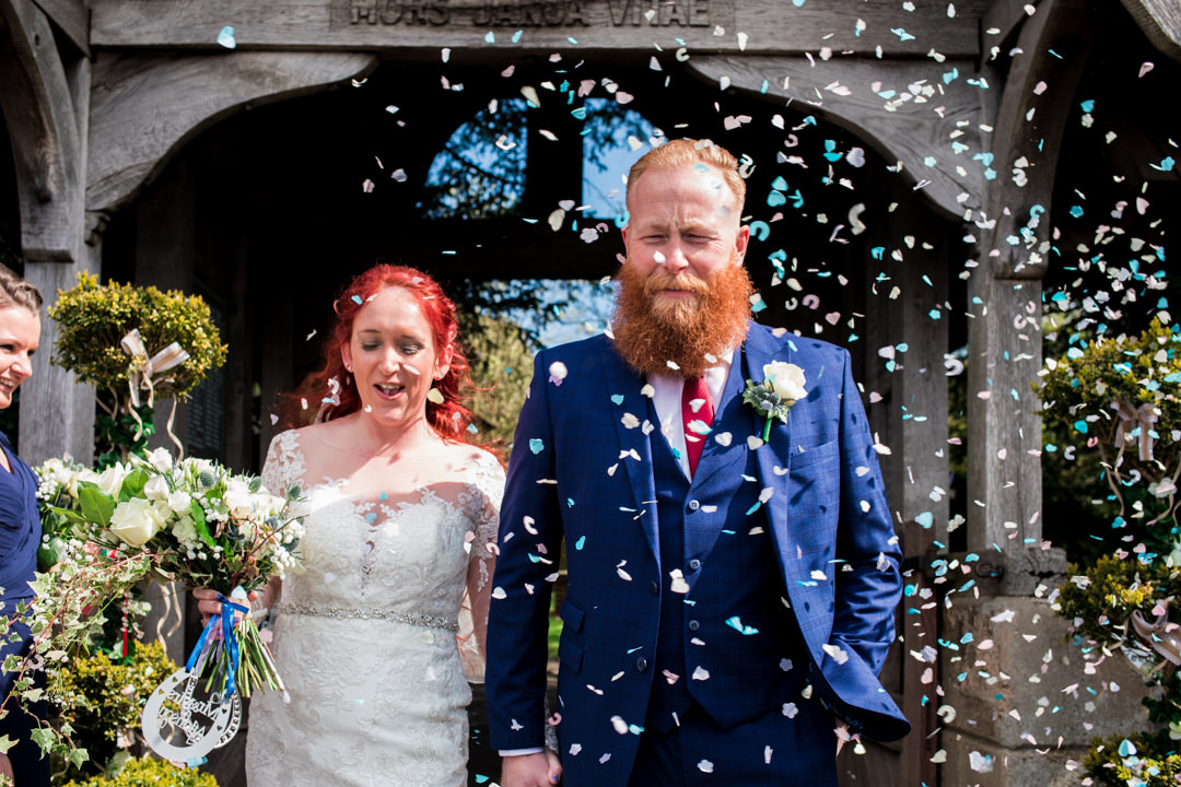 Red haired bride and ginger groom coming out into wedding confetti