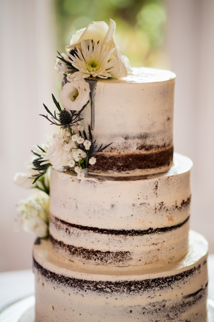Semi naked wedding cake with white flowers