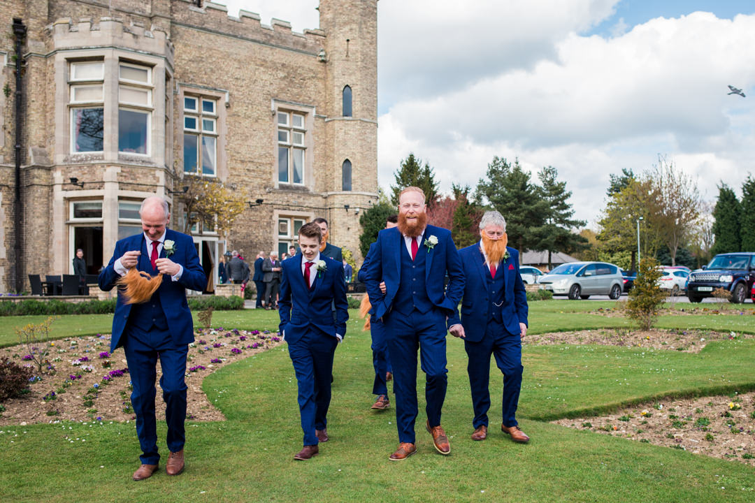Ginger groom and groomsmen in blue suits walking infant of cave castle hotel