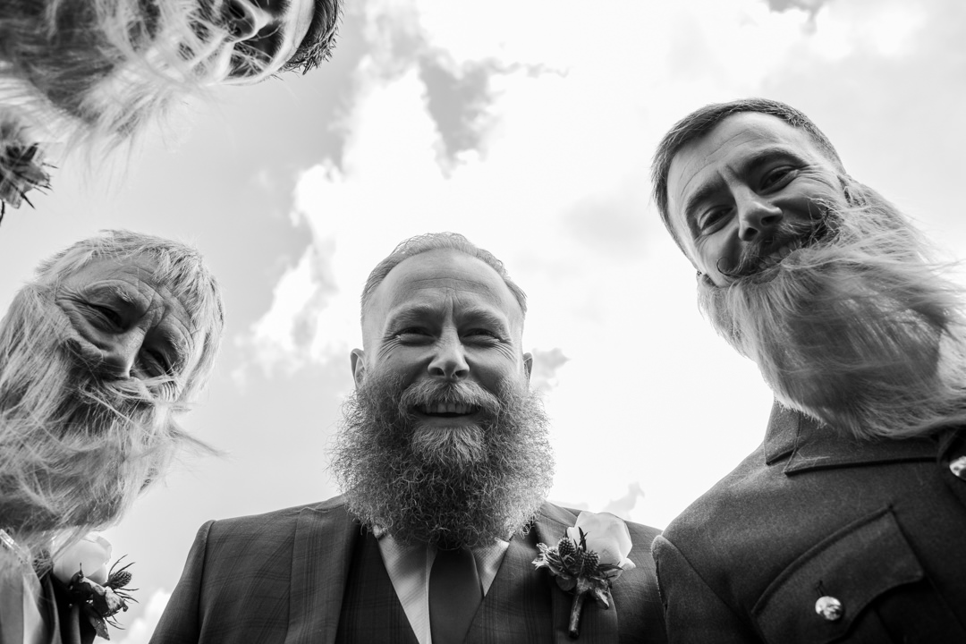 Big bearded groom with groomsmen looking down laughing