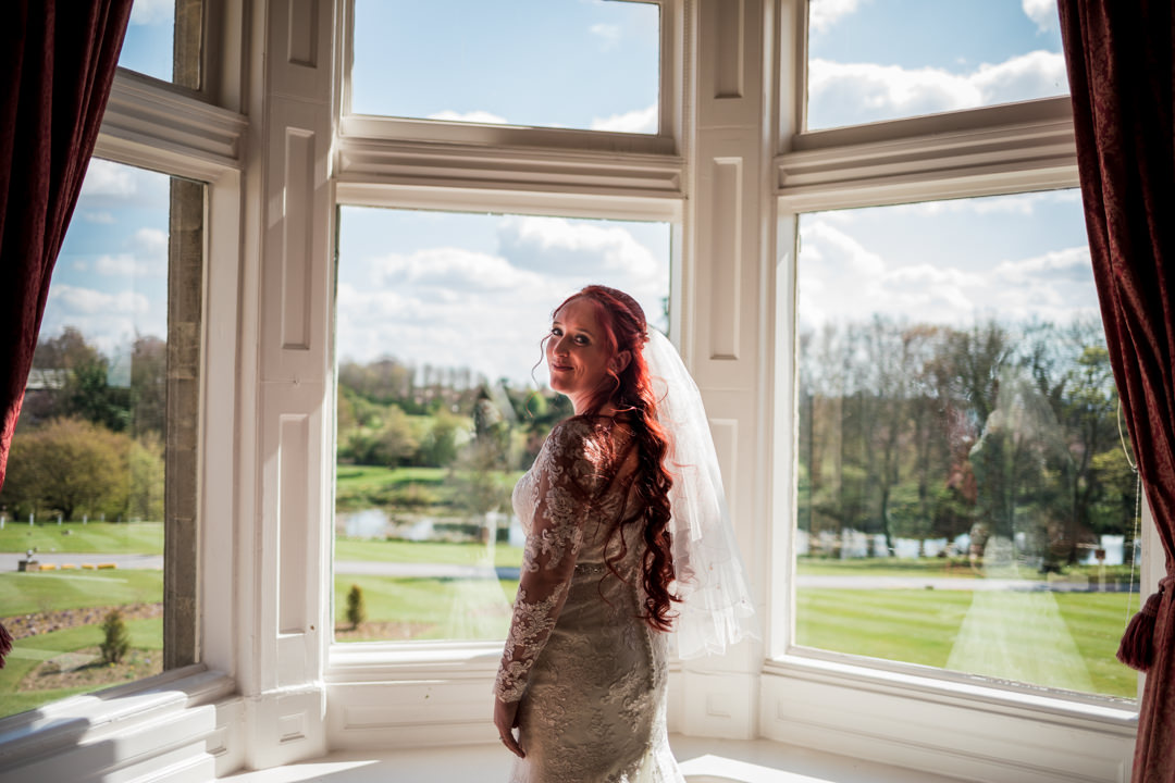 Red haired bride in front of window at cave castle hotel