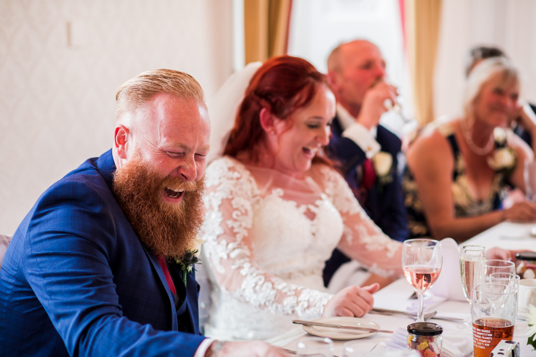 Ginger groom laughing at wedding speech