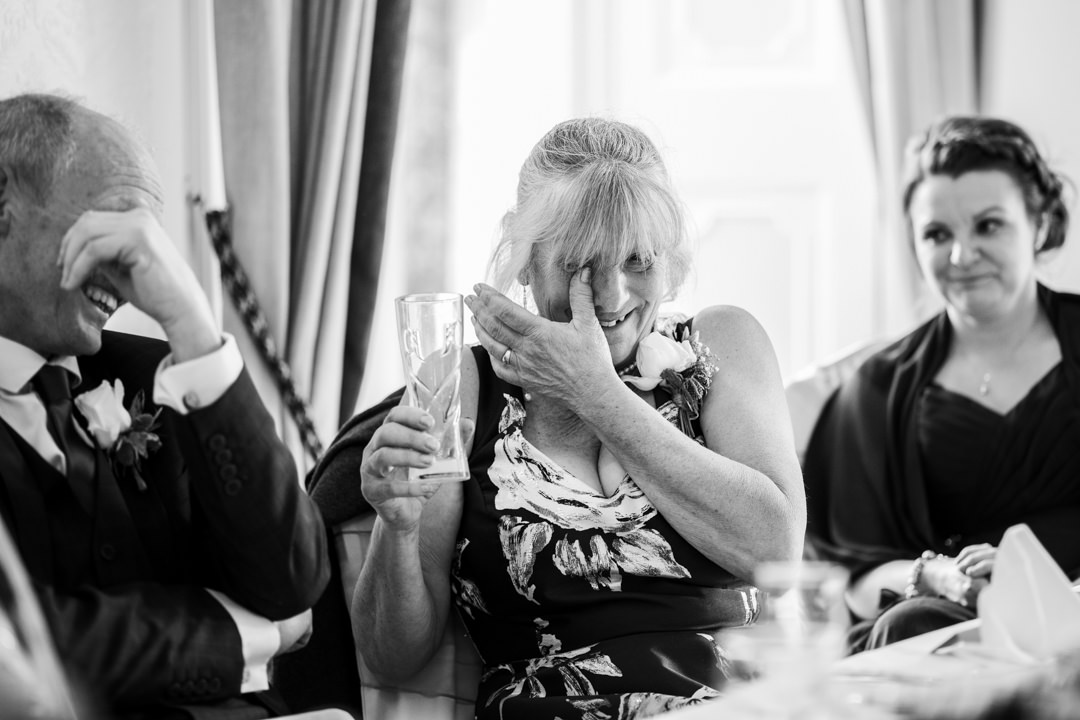 Mother of the bride wiping tear away during wedding speech in black and white
