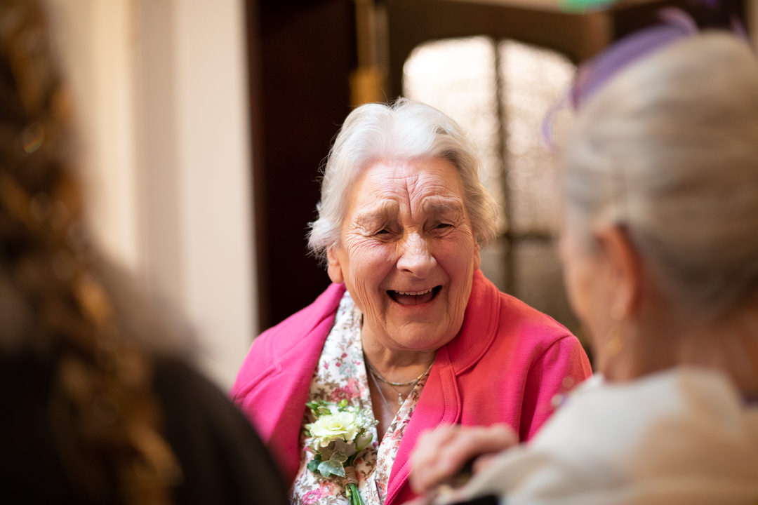 Grandmother of the bride laughing at wedding reception