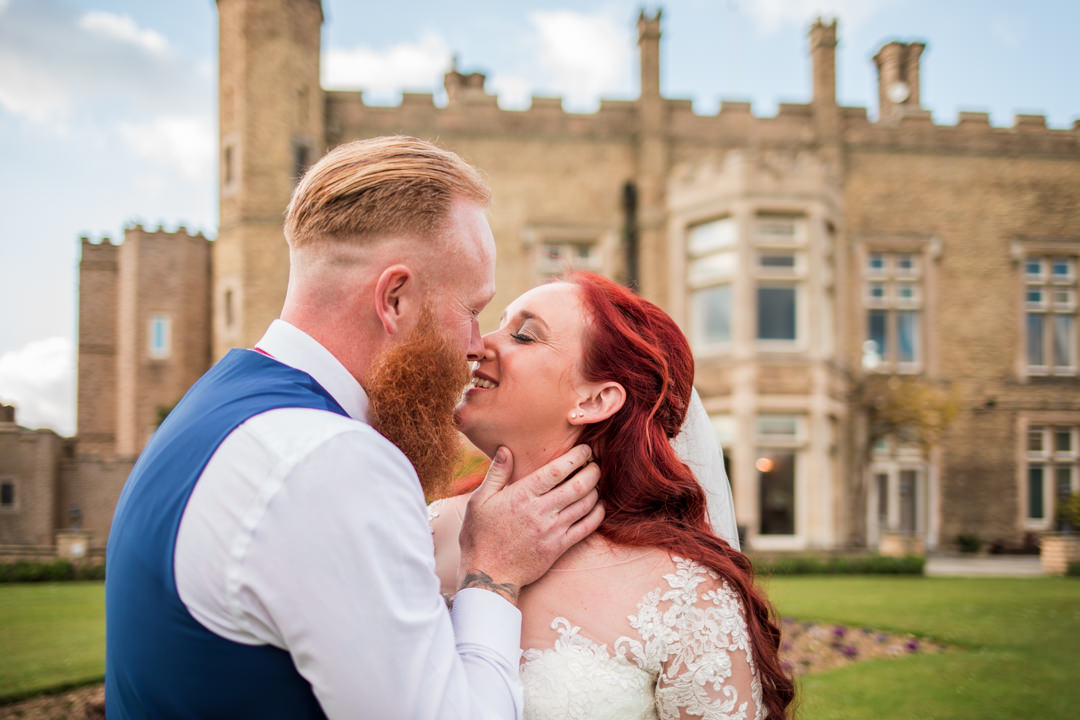Red haired bride and groom kissing in front of cave castle hotel