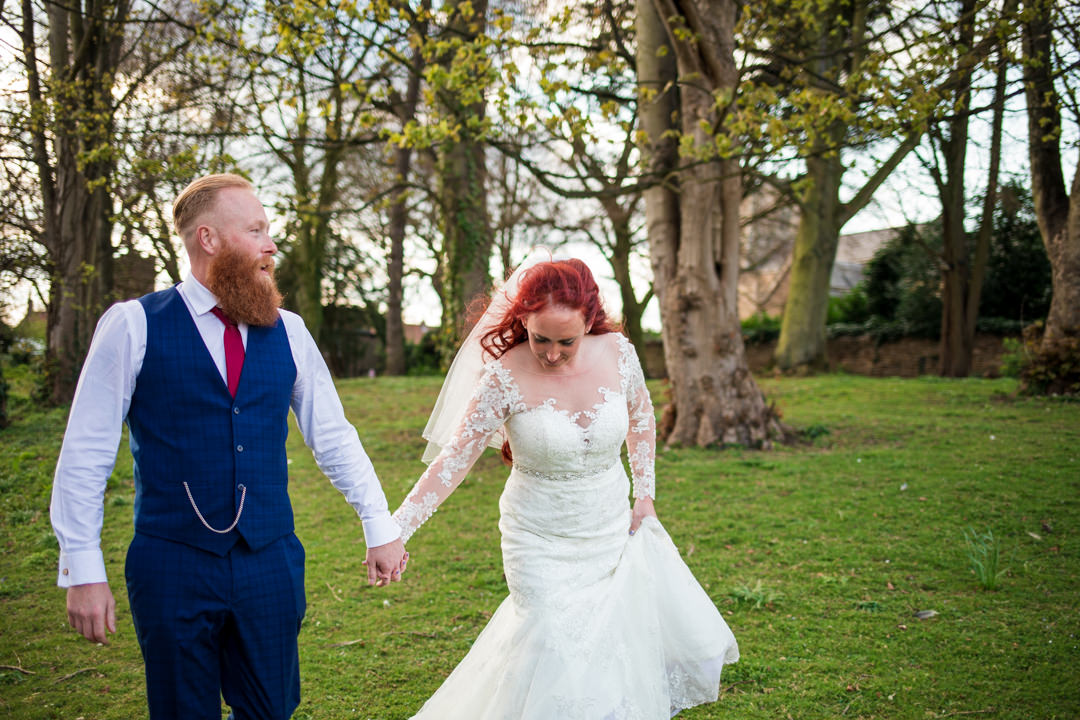 Red haired bride and groom walking through trees