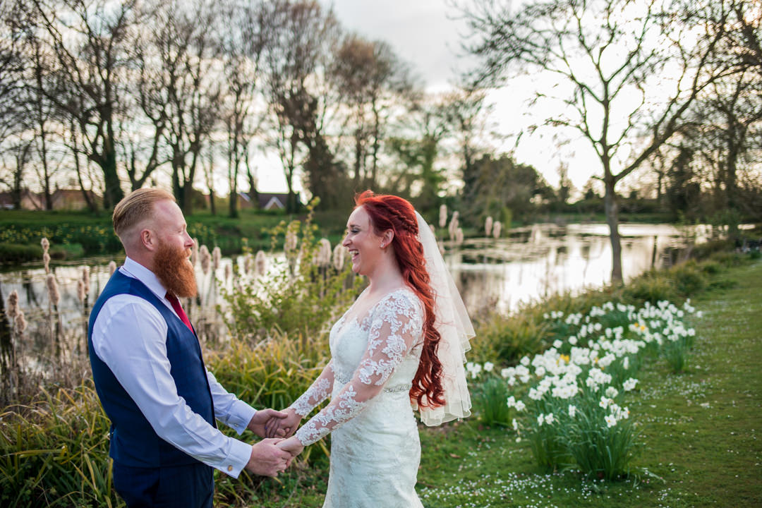 Bride and groom in front of lake in evening light