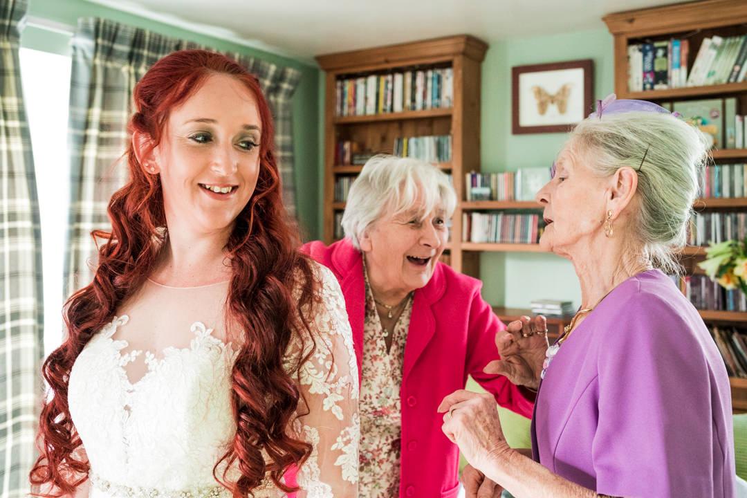 Bride with two grandmothers getting ready
