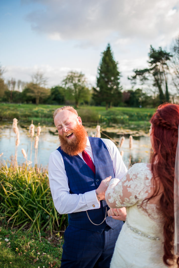Ginger groom holding brides hands and laughing out loud