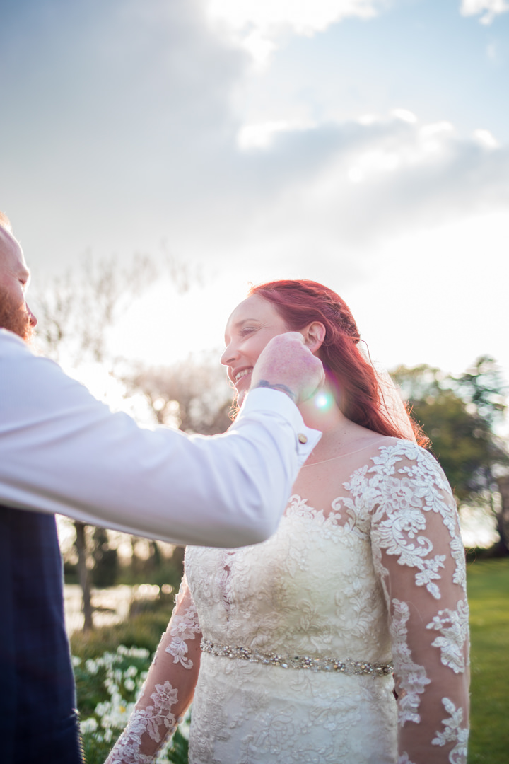 Groom stroking red haired brides cheek in evening light