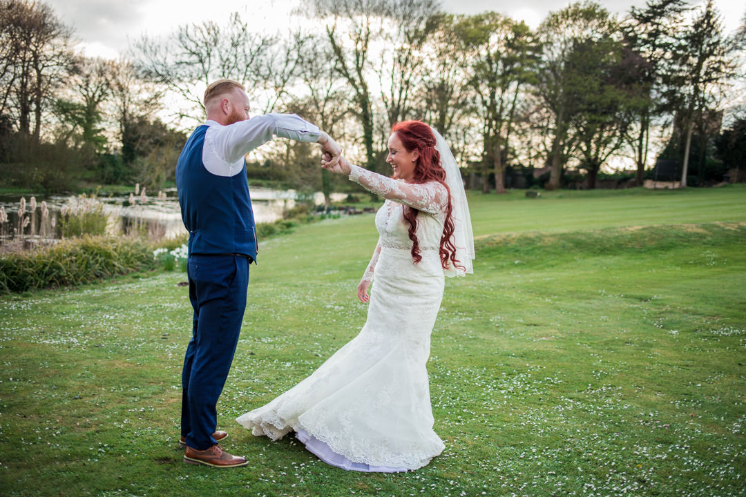 Bride and groom dancing on lawn in evening light