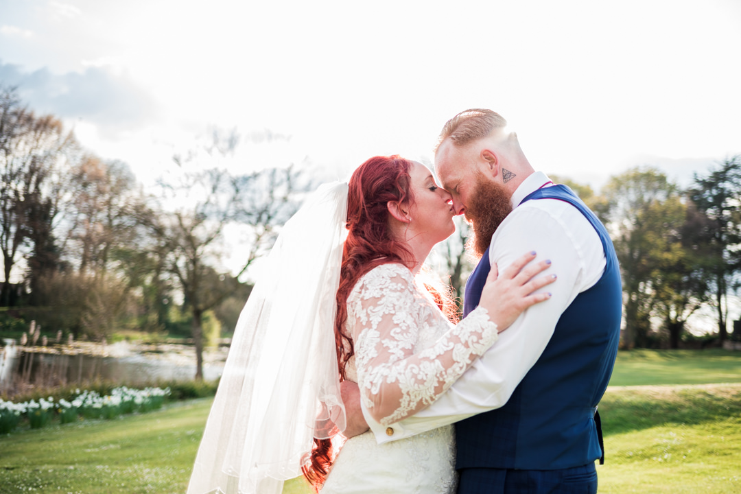 Red haired bride kissing groom on forehead