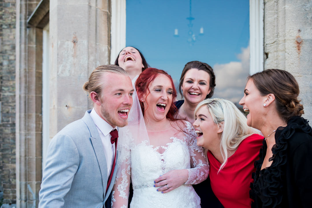 Red haired bride laughing with friends
