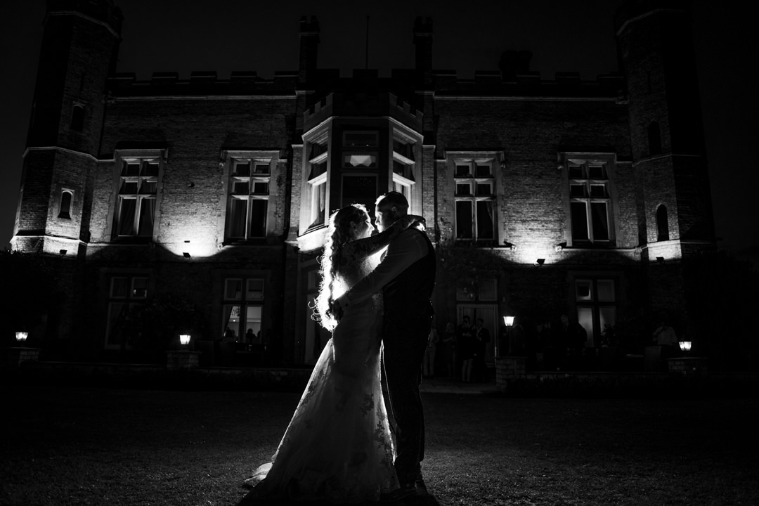 Bride and groom in front of evening lit cave castle hotel